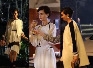 Sühan'ın beyaz elbisesi ve kolları siyah şeritli beyaz kabanı ve minik kare çizgili çanta kombini.