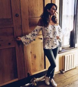 Adı Efsane Seçil Karakterinin Çiçekli beyaz Bluzu Suud İstanbul, kot pantolonu Mavi, Ayakkabısı ise Zuma Shoes marka.