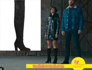 Sühan ın yağmurluk altına giydiği uzun topuklu siyah çizmeler İnci Deri markadır