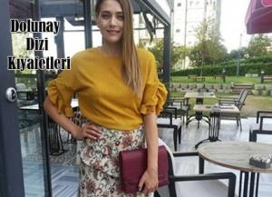 Dolunay dizisi Fatoş vegam mürdüm rengi portföy çantası Pinky Lola Design marka. Fatoş sarı kolları volanlı bluz ve çiçekli etek markası açıklanmadı.